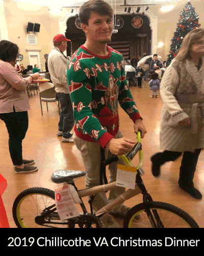 young man in a christams red and green sweater standing with a kids bike