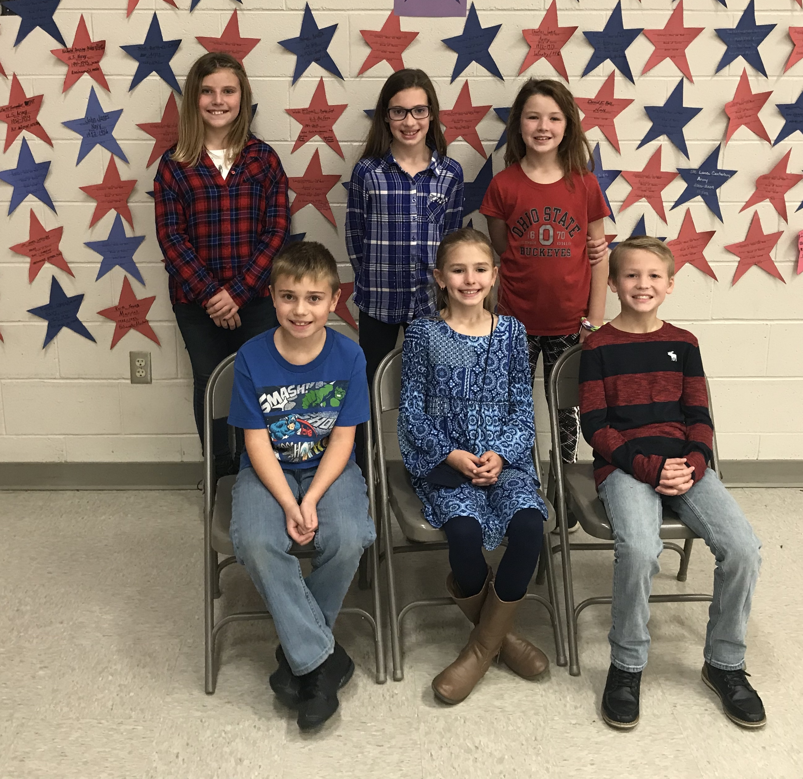 Veterans Day - Goup of girls and boys 3 standing and 3 sitting in front of red and blue paper stars