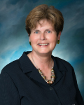 Cathy Chester, Vice President - short brown hair, dark blue shirt, necklace